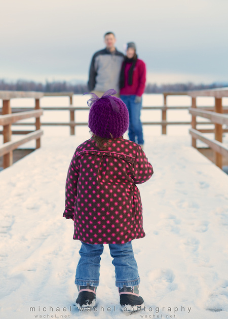 Photo session of little girl looking at parents in Wasilla, AK.